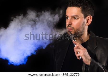 Black haired handsome man vaping e-cirarette mod - blowing cloud of vapor - stock photo
