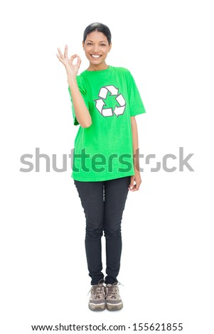 Black haired model wearing recycling tshirt making okay gesture on white background - stock photo