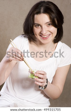 Black-haired woman eating vasabi with a chopsticks