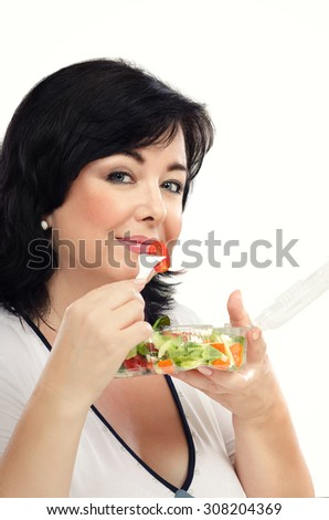 Black haired woman is posing with plastic transparent takeaway container of vegetable salad in left hand. In right hand, she is holding white fork with small cherry tomato. - stock photo