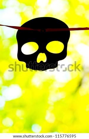 Black Halloween Skull on yellow autumn background - stock photo