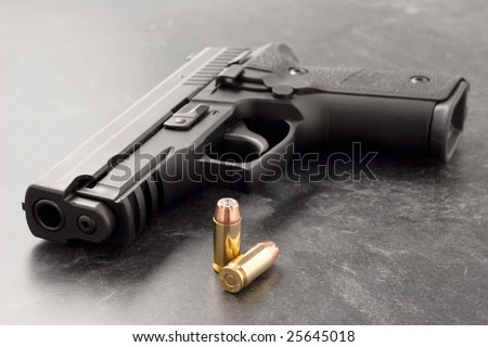 Black hand gun or pistol on black textured surface with hollow point personal defense bullets. - stock photo