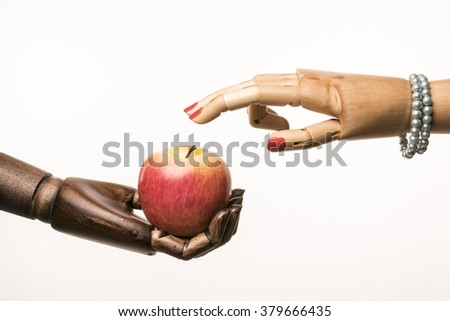 Black hand has an apple. Two fingers of the hand of a woman touching the apple. Interracial couple. The woman's nails are painted red. She wears a pearl bracelet.