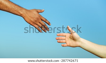 Black hand man helping white person - Different skin color hands united against racism and racial problem - Concept of humane aid between different cultures and religion - friendship between peoples  - stock photo