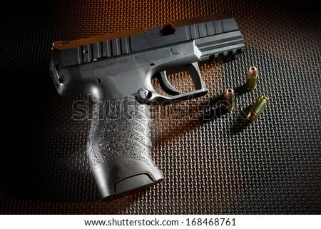 Black handgun with an orange gel on a dark background - stock photo