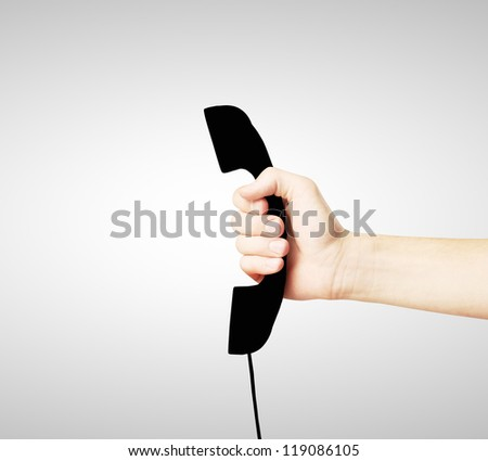 black handset sign in hand, closeup - stock photo