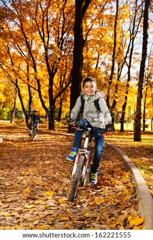 Black happy 10 years old boy riding a bicycle in the autumn park