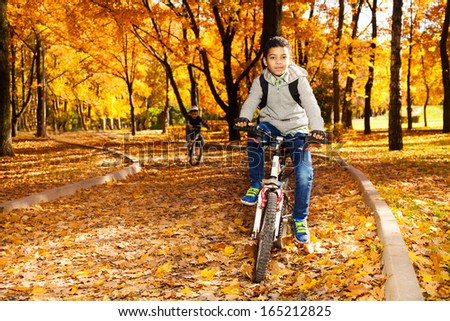 Black happy 10 years old boy riding a bicycle in the autumn park with his little brother