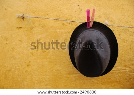 black hat against a yellow wall - stock photo