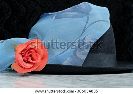 Black hat with a blue scarf with the motif of roses red rose on a marble table, fashion - stock photo