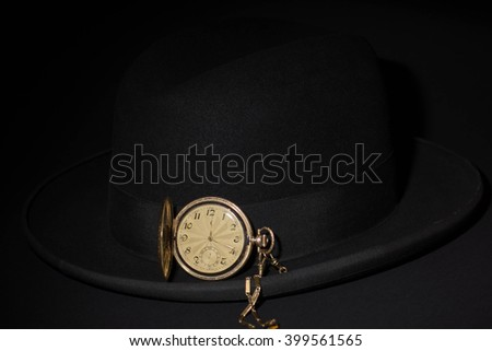 Black hat with a pocket watch on a black background - stock photo