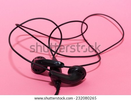 Black headphones on pink background - stock photo