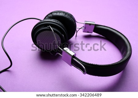 Black headphones on purple background