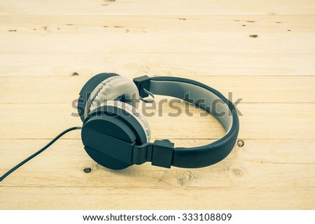 Black Headphones on wood desk Background. Vintage color tone.