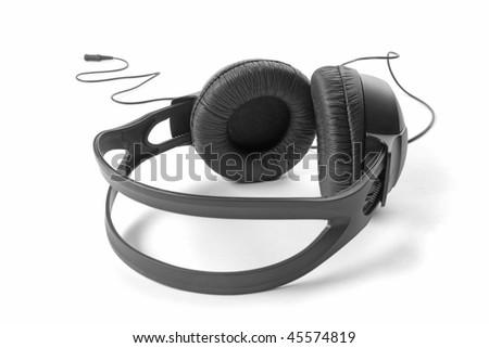 Black headphones with cord on white ground - stock photo