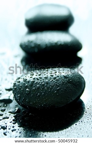 Black healing stones on a wet black surface - stock photo