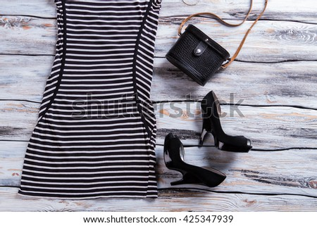 Black heel shoes and dress. Dark footwear with classic purse. Woman's new clothing on showcase. Special offer with low price.