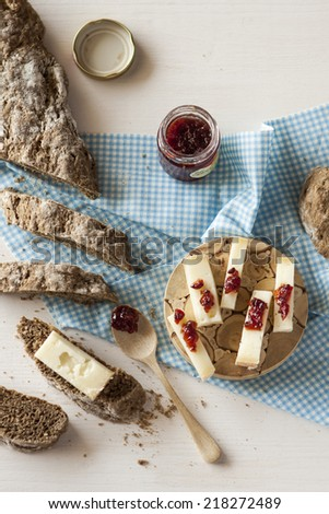 Black homemade bread sliced with cheese and jam - stock photo