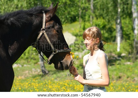 Black horse with girl in a field - stock photo