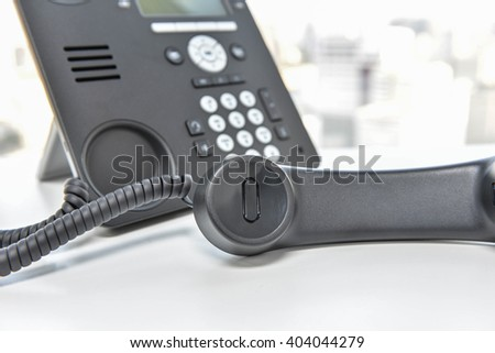 Black IP phone on the white desk