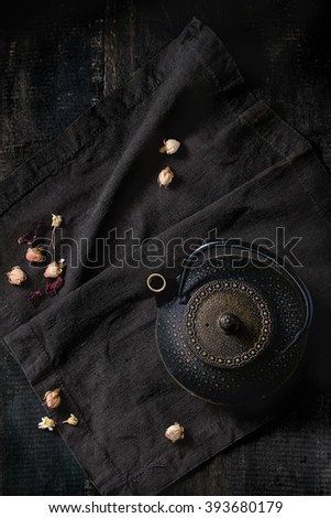 Black iron asian style teapot with dry tea roses on black textile napkin over old wooden table. Flat lay. - stock photo
