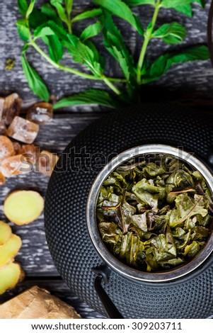 Black iron asian tea set with green tea leaves, closeup view - stock photo
