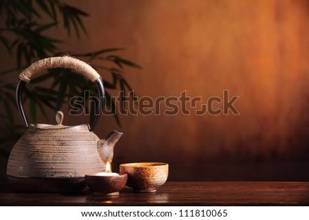 Black iron asian teapot and burning candle,vintage style. - stock photo