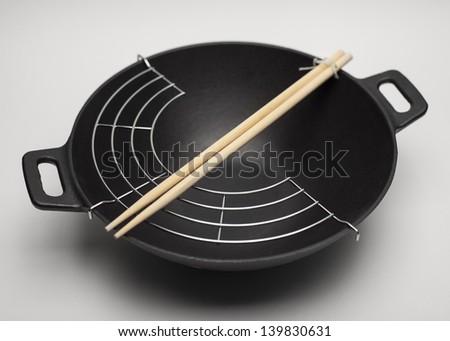 Black iron cast wok with chopsticks on white background - stock photo