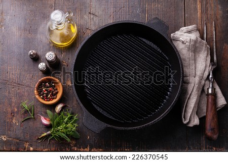 Black iron empty grill pan and meat fork on wooden texture background - stock photo