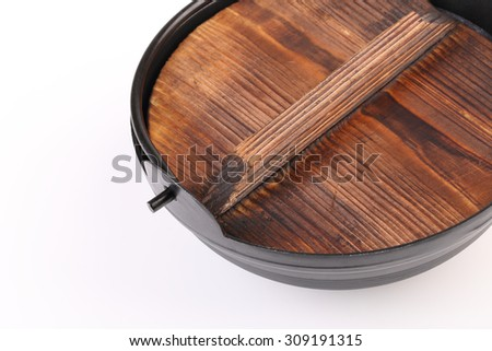 Black iron pot with wooden lid  isolated on white background.