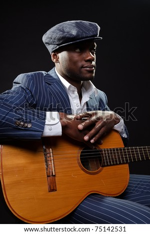 Black jazz musician wearing suit and blue cap playing guitar.