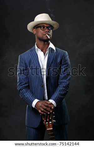 Black jazz musician wearing suit and white hat standing with guitar. Smoking cigarette and wearing glasses.