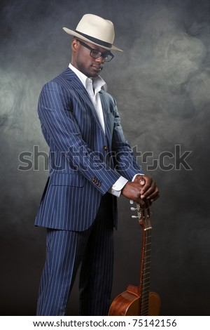 Black jazz musician wearing suit and white hat standing with guitar. Smoking cigarette and wearing glasses. - stock photo