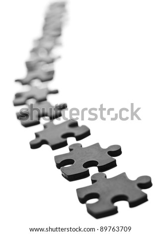Black Jigsaw pieces in a row isolated on white - stock photo