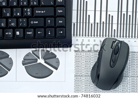Black keyboard and mouse on a stock chart. - stock photo