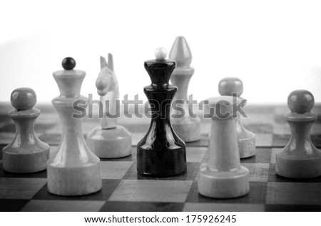 black king surrounded by white chess pieces on a chess board
