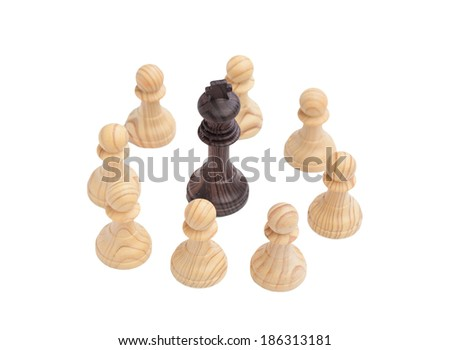 Black King surrounded by white pawns. Wooden chess piece on chessboard