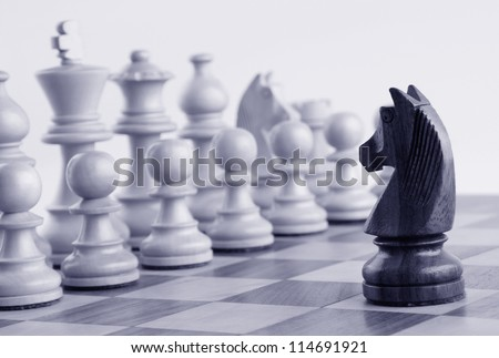 Black knight facing white chess pieces on a chess board - stock photo