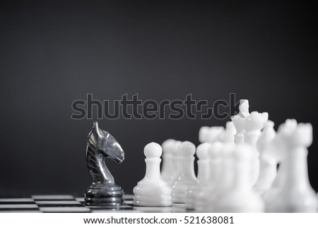 Black knight on a chess board alone against all white pieces. Black knight fights against white enemy team on board.