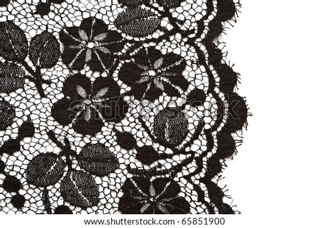 Black lace on the white fabric background. - stock photo