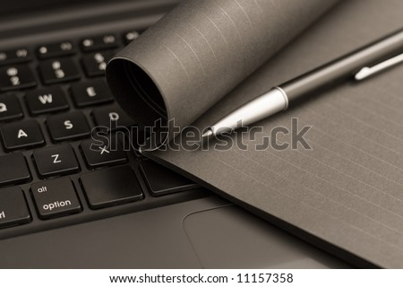 Black laptop, black notebook and black pen. Focus on the area around the corner of the book and the pen tip. - stock photo
