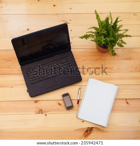 Black laptop computer on the wooden background - stock photo