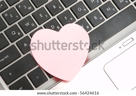 Black laptop keyboard with pink sticker