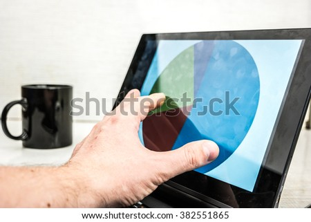 Black laptop with business charts on screen, on white table in office. Hand using the touchscreen. With coffe cup in background.