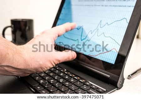 Black laptop with business charts on screen, on white table in office. Hand using the touchscreen. With coffe cup in background. - stock photo