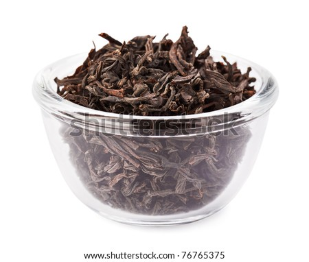 Black leaf tea heap in transparent glass bowl, isolated on white