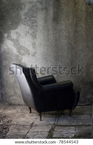 black leather armchair turned to a concrete  wall