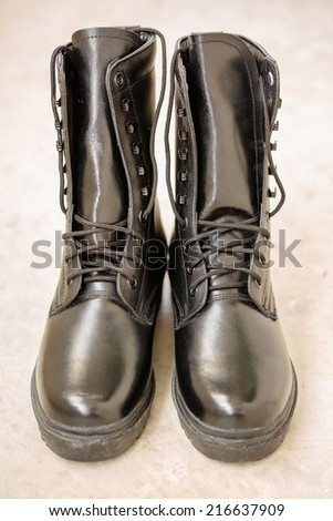 Black Leather Army Boots on blare cement floor - stock photo