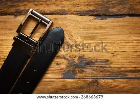 black leather belt for men on wooden table - stock photo