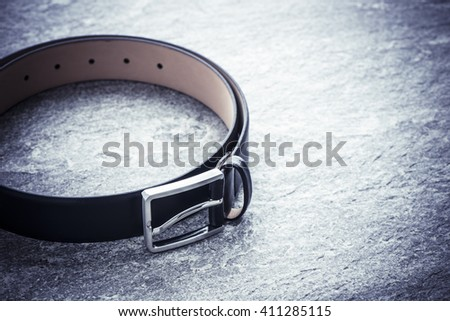 Black leather belt on stone surface. Still life image of clothes accessory.
